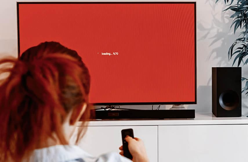 woman sitting in her living room and holding a TV remote control in front of a screen display waiting message