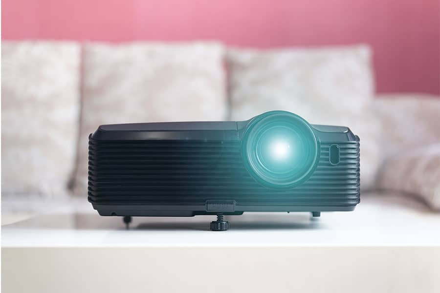 Projector with it's lamp on that's located in front of a couch