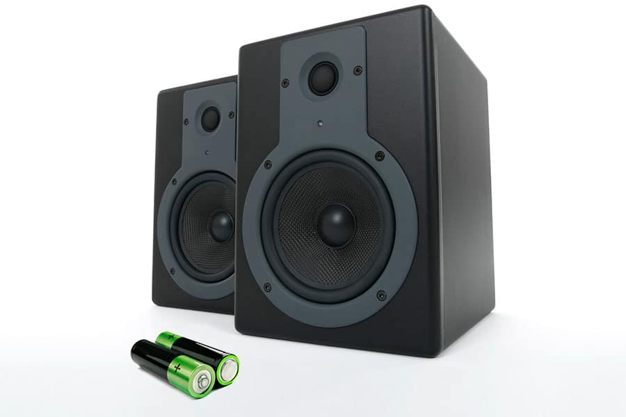 2 Bookshelf speakers with 2 AA batteries on a white background