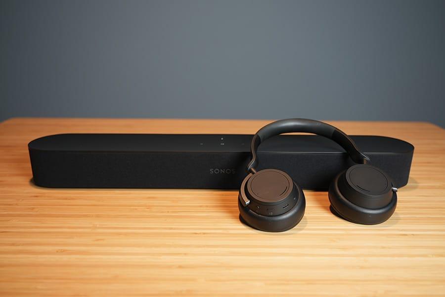 Sonos Beam Soundbar and Microsoft Surface Headphones on a Wood Desk