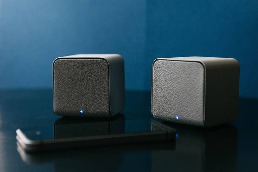 Wireless speakers and a cell phone next to them on a dark background